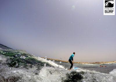 Mann steht auf Surfbrett
