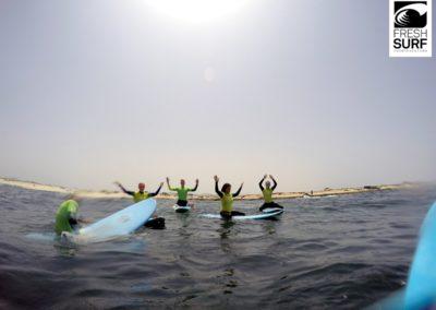 Surfschüler haben Hände hoch
