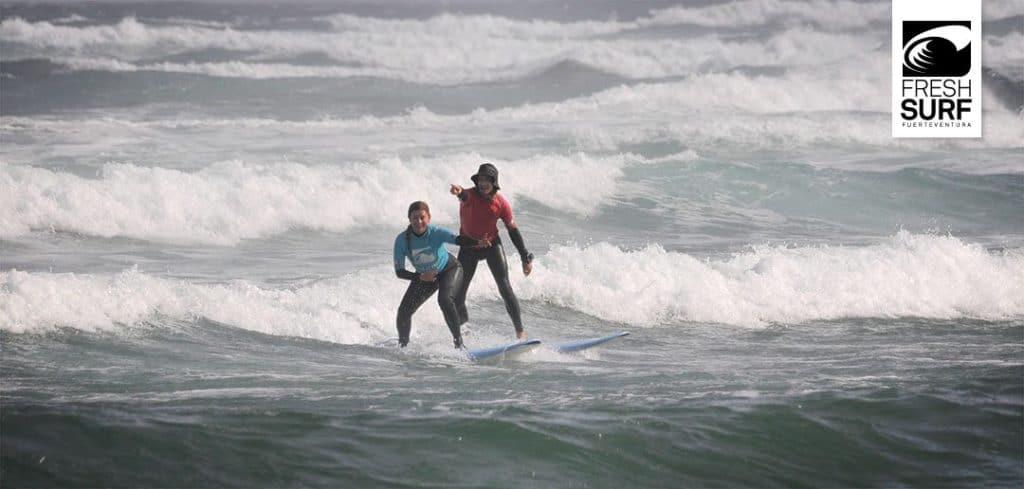 Surfschülerin und Coach in den Wellen
