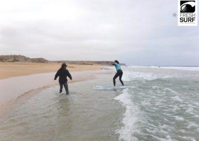 Surfschülerin surft bis an den Strand